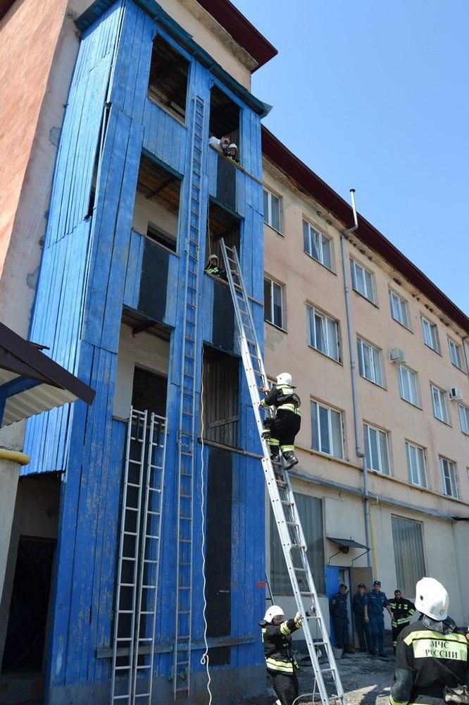 Установка трехколенной выдвижной лестницы к стене здания